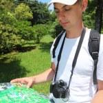 Photographer looks on map in sochi arboretum — Stock Photo