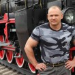 Strong man against locomotive — Stock Photo