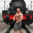 Strong shirtless man stands on railroad against locomotive - Stockfoto