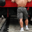 Strong shirtless man pushs locomotive — Stock Photo