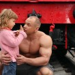 Strong shirtless man sits on railroad with little girl — Stock Photo
