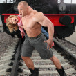 Strong shirtless msaving little girl on railroad — Stock Photo #7429389
