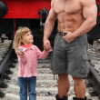 Strong shirtless man stands on railroad with little girl — Stock Photo