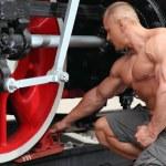 Athlete puts brake boot under locomotive wheel — Stock Photo