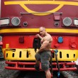 Shirtless athlete stands on railroad against locomotive — Stock Photo #7429450