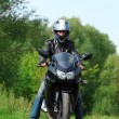Motorcyclist standing on country road — Stock Photo
