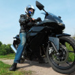 Постер, плакат: Motorcyclist standing on country road bottom view
