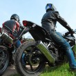 Two motorcyclists standing on country road, back view — Foto Stock
