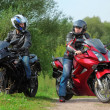 Two motorcyclists standing on country road looks on each other — Stock Photo