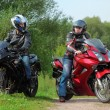 Two motorcyclists standing on country road looks on each other — Stock Photo #7429483