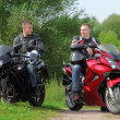 Two motorcyclists standing on country road, without helmets — Stock Photo #7429485