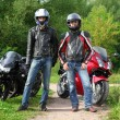 Two motorcyclists standing on country road near bikes — Stock Photo #7429487