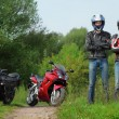 Two motorcyclists standing on country road near bikes — Stock Photo #7429490
