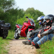 Two motorcyclists sitting on country road near bikes — Stock Photo #7429494