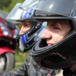Portrait of two motorcyclists sitting on country road near bike - Stock Photo