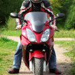 Motorcyclist standing on country road — Stock Photo #7429507