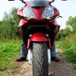 Постер, плакат: Motorcyclist standing on country road closeup front view