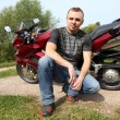 Motorcyclist sitting on country road near bike — Stock Photo #7429534