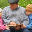 Grandfather reads book for kid — Stock Photo