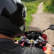Motorcyclist on country road, view  because of shoulder — Stock Photo
