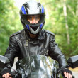 Постер, плакат: Motorcyclist goes on road front view closeup