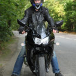 Motorcyclist standing on road — Stock Photo