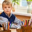 Young schoolboy sitting Behind a school desk - Stock Photo
