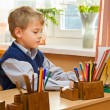 Stock Photo: Young schoolboy sitting Behind a school desk