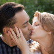 Married couple kissing outdoors — Stock Photo