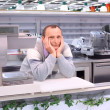 Bored seller in shop with empty shelves and counters — Stock Photo #7429617