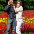 Young couple in flowering park — Stock Photo #7429640