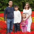 Family of four persons in flowering park — Stock Photo