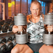 Strong bodybuilder training muscles in gym — Stock Photo