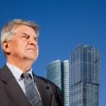 Senior man near skyscrapers construction — Stock Photo #7429715