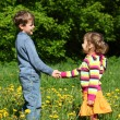 Boy and  girl handshaking among blossoming dandelions - Foto Stock