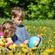 Two children with globe sit on meadow among blossoming dandelion — Stockfoto