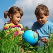 Royalty-Free Stock Photo: Girl and boy with globe on meadow