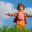 Little girl on grass against sky — Stock Photo
