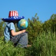 Boy in big american flag hat sits on  grass and holds globe - Stockfoto
