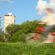 Bicyclist in motion blur against trees and houses - Stock Photo