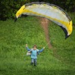 Boy runs from hill with parachute - Stock Photo