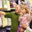 Family with little girl buy bedding in supermarket - Foto Stock