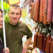 Smiling young man and woman buy sausage in supermarket — Stok fotoğraf
