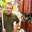 Smiling young man and woman buy sausage in supermarket — Foto Stock
