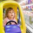 Little girl goes for drive on shoppingcarts in supermarket - Stock Photo