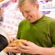 Smiling young man and woman buy chicken in supermarket — Stockfoto