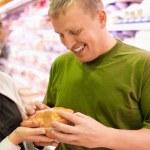 femme et souriant jeune homme achètent poulet en supermarché — Photo