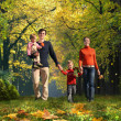 Walking family with two children in autumnal park collage — Stock Photo