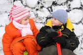 Girl and boy at snow wall — Stock Photo