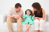 Parents and daughter on white leather sofa — Stock Photo